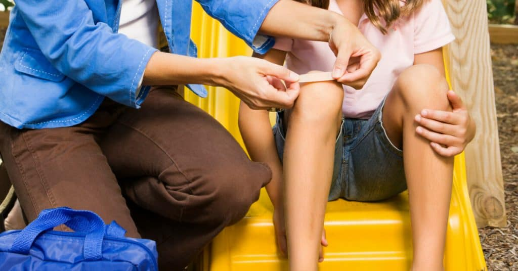 woman putting band-aid on child's knee