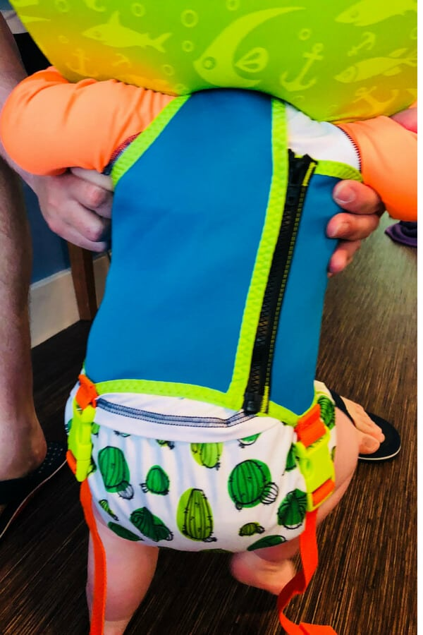 Backside of baby wearing green and blue puddle jumper life jacket. Swim diaper with cacti visible.