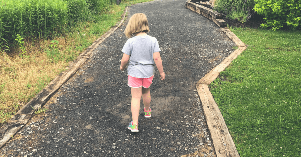 Child on gravel path with back to camera