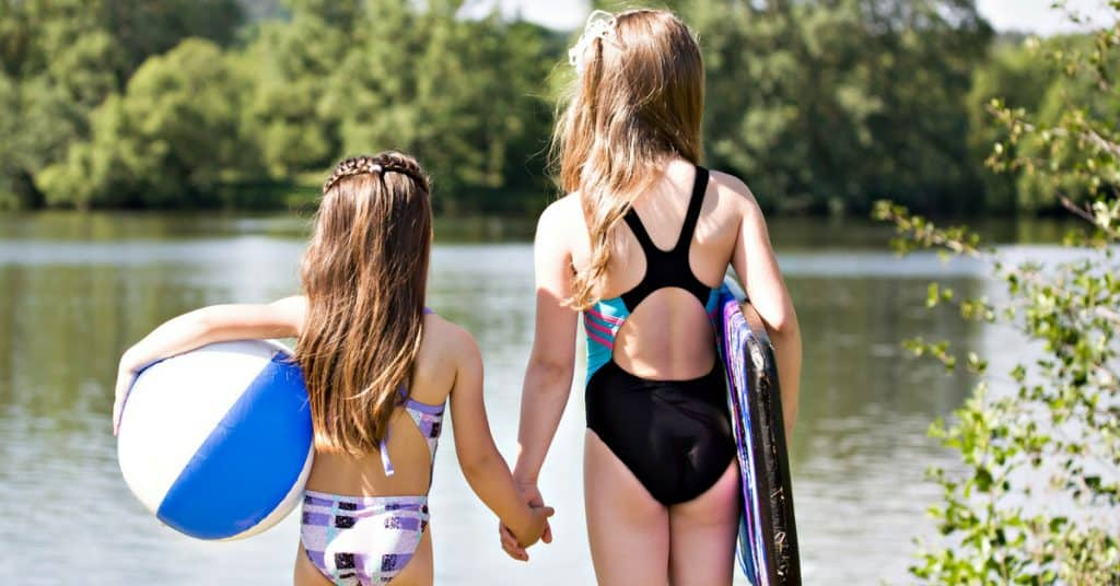 back of two girls in swimsuits holding hands. Girls are facing a lake.