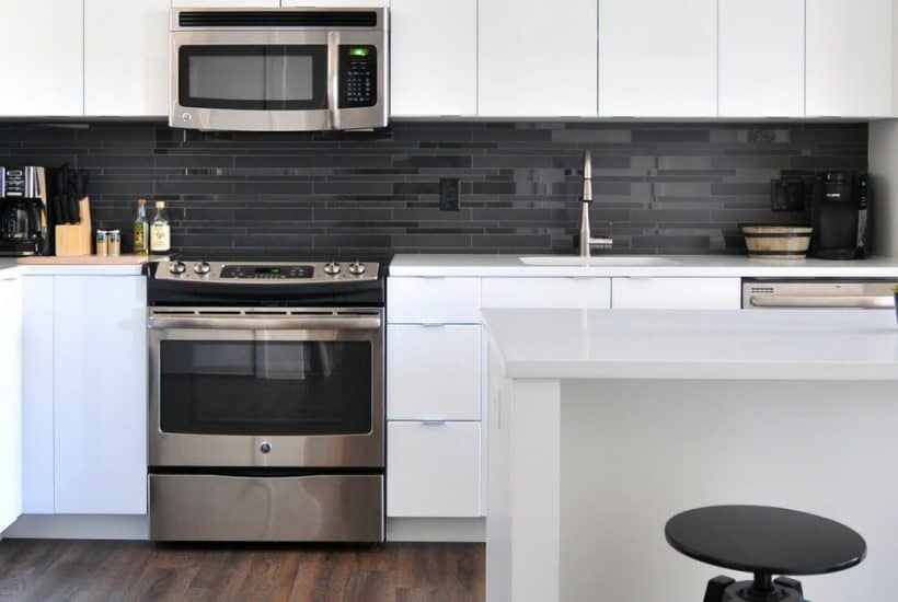 Image of kitchen with white countertops and stainless steel appliances