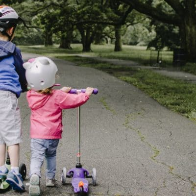 back view of two children riding scooters down the street