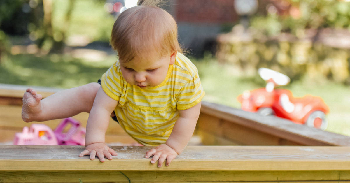 image of infant climbing out of sandbox
