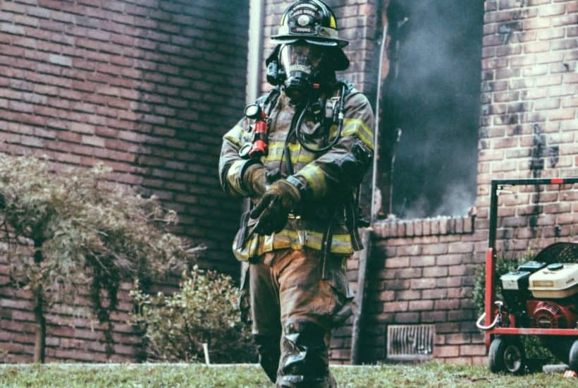 image of fire man outside burning home