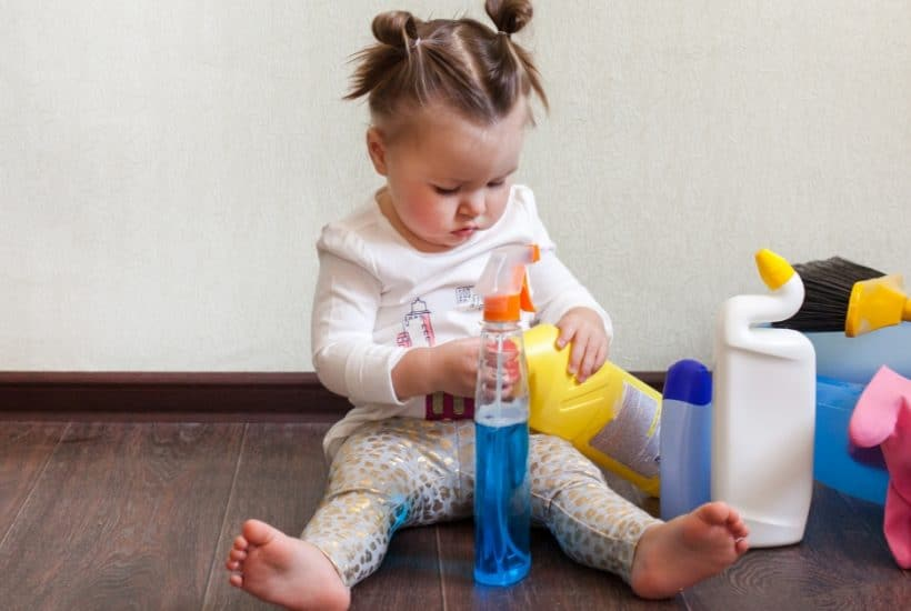 child sitting on floor surrounded by bottles of cleaning solution
