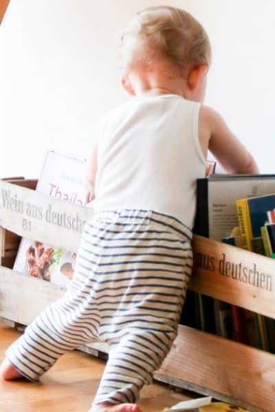 image of child leaning into bin of books