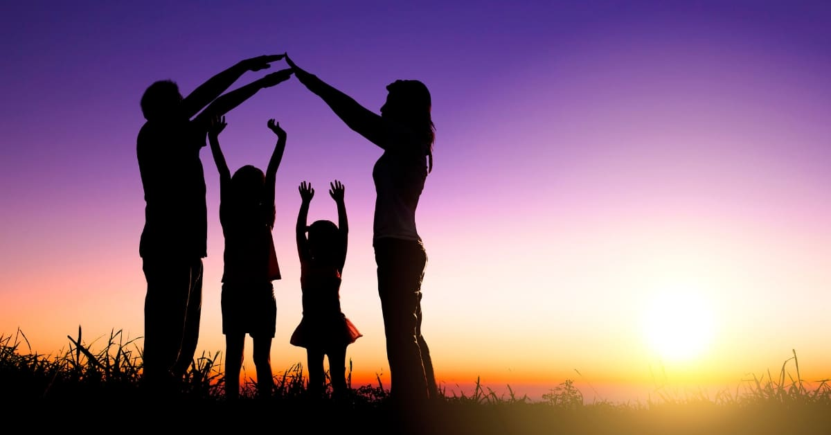 image of family standing together in sunset