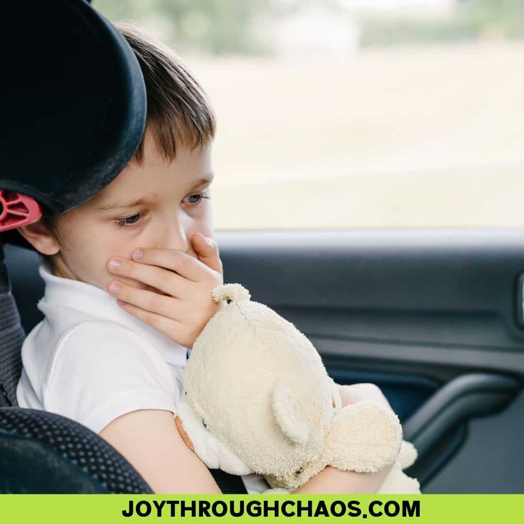 Image of child in carseat with hand over mouth, nauseated